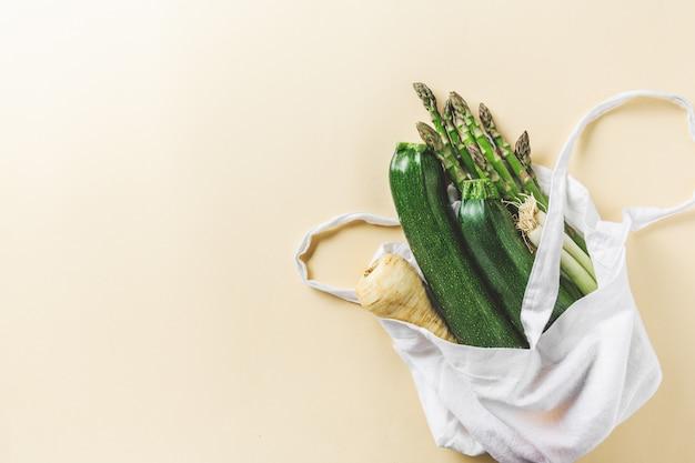 Vegetais diferentes em saco têxtil na copyspace amarelo Foto Premium