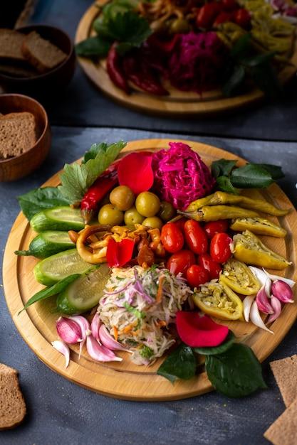 Vegetais diferentes tomates azeitonas pimenta verde e outros vegetais na mesa marrom Foto gratuita