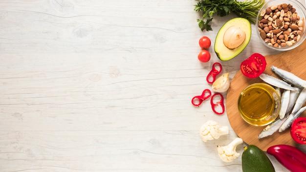 Vegetais saudáveis; frutas secas; óleo e peixe cru na mesa de madeira Foto gratuita