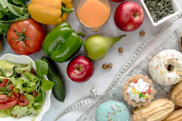 Vegetais saudáveis; suco; fruta; comida doce; sementes de abóbora e avelãs com fita métrica Foto gratuita