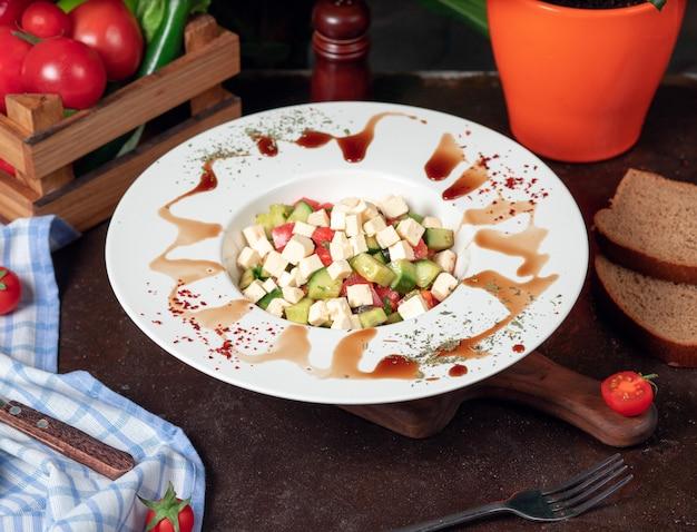 Vegetal, tomate, pepino, salada de roka. salada com sumakh e limão na mesa da cozinha dentro de chapa branca Foto gratuita