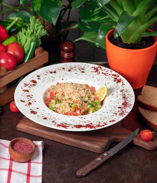 Vegetal, tomate, salada de pepino com bolachas. salada com sumakh e limão na mesa da cozinha dentro de chapa branca Foto gratuita