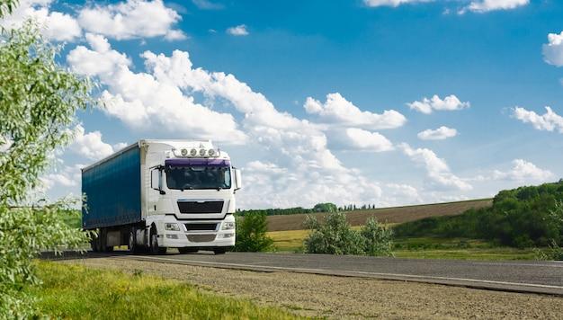Veículo de caminhão europeu com contêiner na rodovia e céu azul com nuvens. Foto Premium