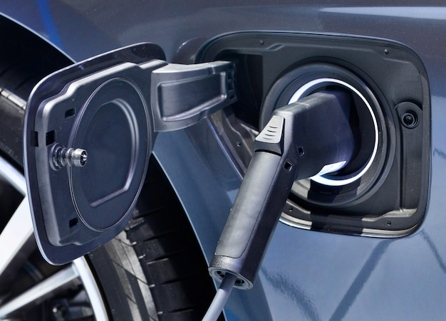 Veículo elétrico que carrega na estação com a fonte de alimentação obstruída em um carro elétrico que está sendo carregado. Foto Premium