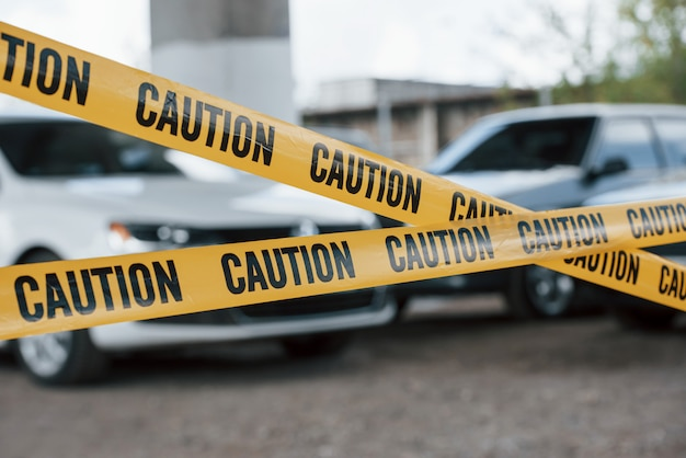 Veículos preto e branco. fita isolante amarela perto do estacionamento durante o dia. cena do crime Foto gratuita