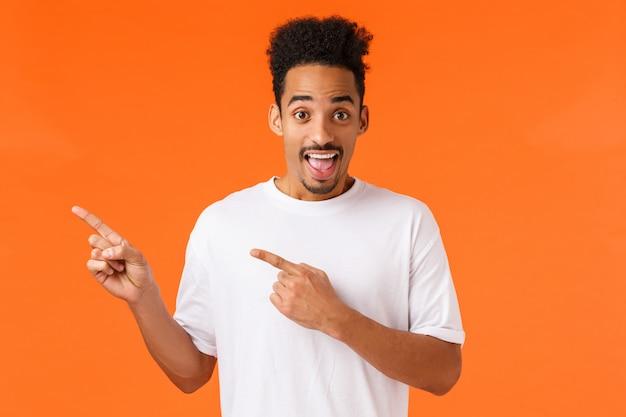 Veja bem, confira. divertido e animado alegre hipster afro-americano cara de camiseta branca, apontando o canto superior esquerdo e sorrindo, sugerir lugar incrível, apresentar o produto, laranja Foto Premium