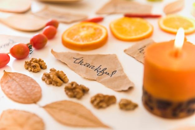 Vela acesa perto de notas, frutas e folhas Foto gratuita