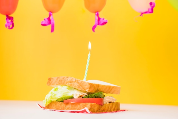 Vela acesa sobre o sanduíche contra fundo amarelo Foto gratuita
