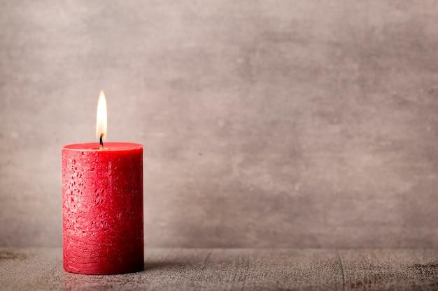 Vela acesa vermelha sobre um fundo cinza. artigos para interiores. Foto Premium