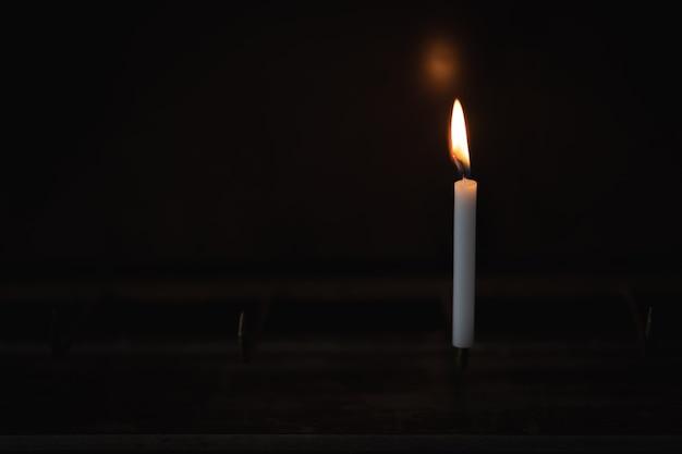 Vela de luz brilhando em preto Foto Premium
