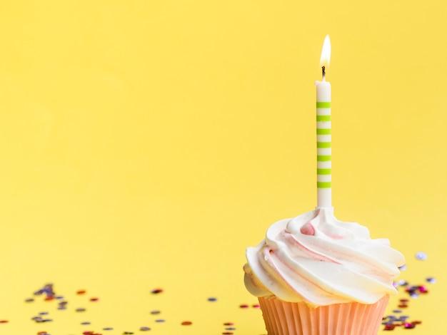 Vela e muffin de aniversário simples close-up Foto gratuita