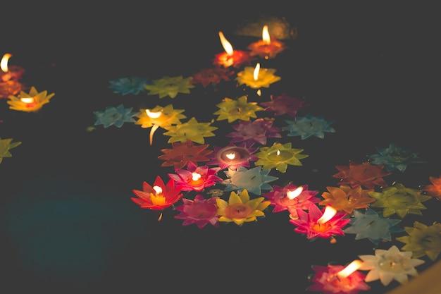 Vela em forma de flor queimando na piscina de espírito no templo chinês Foto Premium