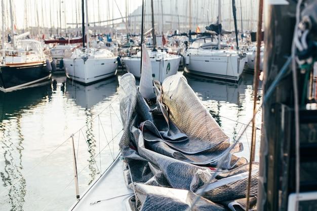 Vela mestra ou balão baixado e dobrado no convés de um veleiro ou iate de luxo profissional, ancorado no pátio ou na marina Foto gratuita