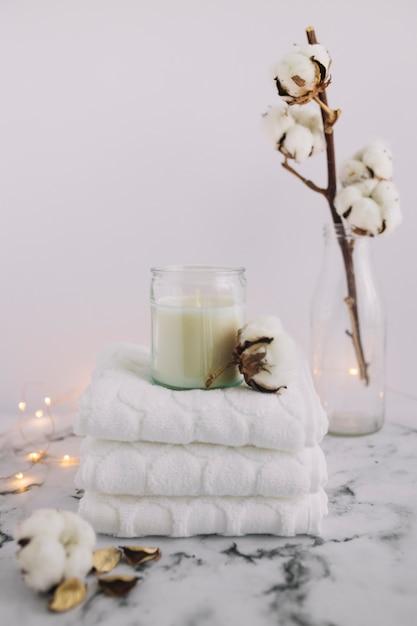 Vela no castiçal com guardanapos empilhados perto de galho de algodão e equipamentos de iluminação na superfície de mármore Foto gratuita
