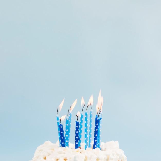 Velas acesas azuis sobre o bolo de aniversário contra o pano de fundo azul Foto Premium