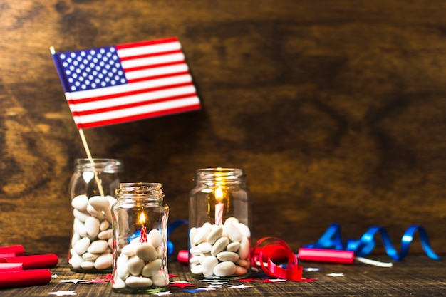 Velas acesas e bandeira eua no pote de doces na mesa de madeira Foto gratuita