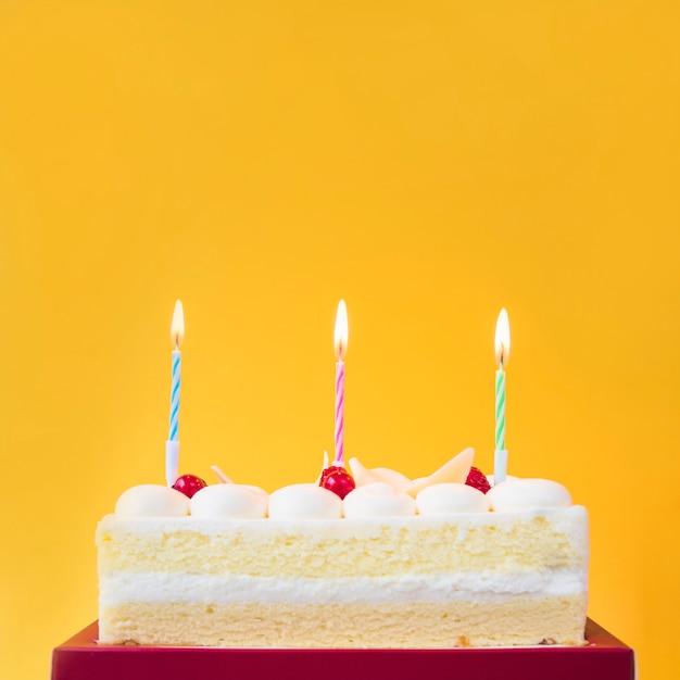 Velas acesas no bolo doce contra um fundo amarelo Foto gratuita