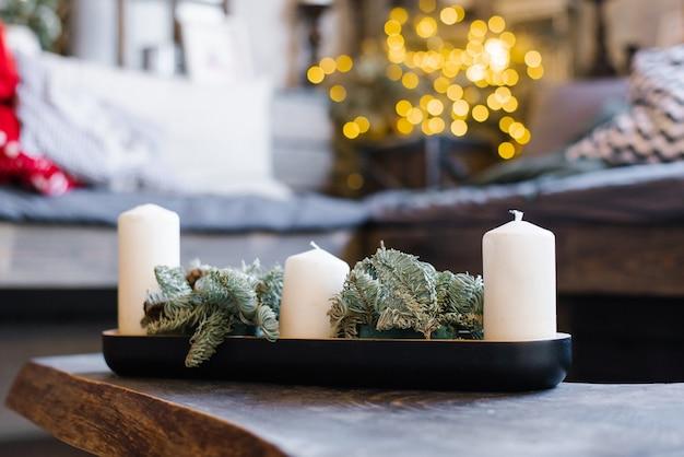 Velas brancas e galhos de pinheiro na decoração natalina Foto Premium