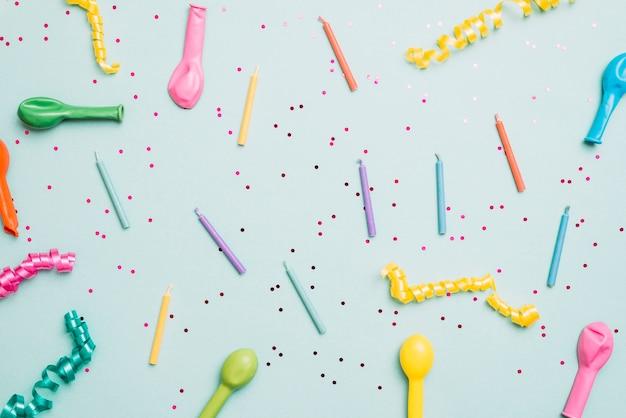 Velas coloridas; balões vazios e flâmulas em fundo azul Foto gratuita