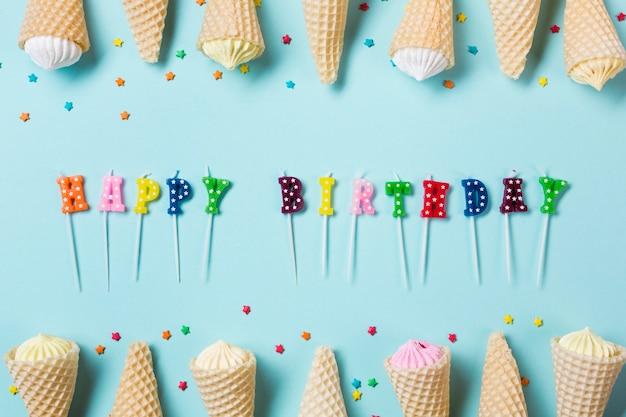Velas coloridas do feliz aniversario decoradas com aalaw no cone do waffle no fundo azul Foto gratuita