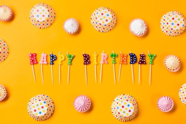 Velas coloridas do feliz aniversario decoradas com formulários do bolo do papel do aalaw e das bolinhas no fundo amarelo Foto gratuita