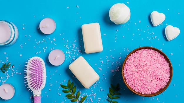 Velas com sabão; bomba de banho; escova de cabelo e rosa sal no pano de fundo azul Foto gratuita
