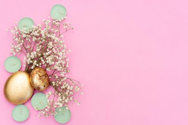 Velas de hortelã no fundo rosa, flores secas e folha de ouro Foto Premium