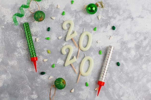 Velas em forma de números 2020 como um símbolo do ano novo ao lado de natal em forma de doces de brilho em uma mesa cinza. vista superior, plana Foto gratuita