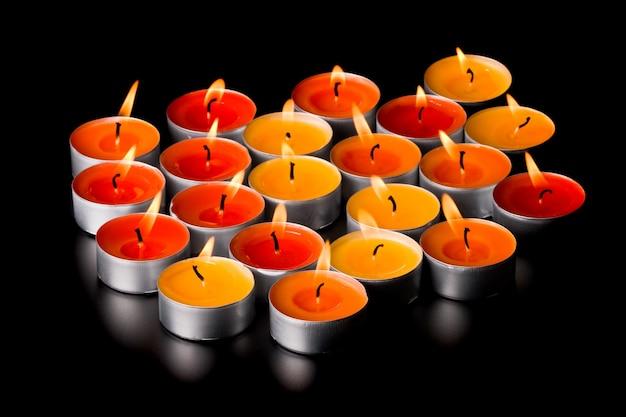 Velas flamejantes em fundo preto Foto Premium