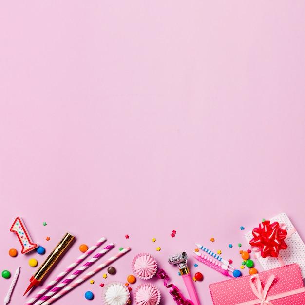 Velas; gemas; canudo; granulados; caixas de presente; flâmula; aalaw na parte inferior do pano de fundo rosa Foto gratuita