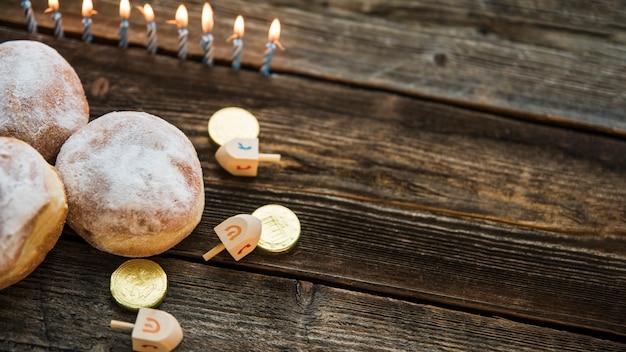 Velas perto de donuts e símbolos de hanukkah Foto gratuita