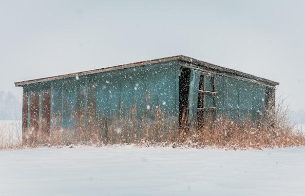 Velha e abandonada cabana azul de madeira em uma área deserta durante a tempestade de neve Foto gratuita
