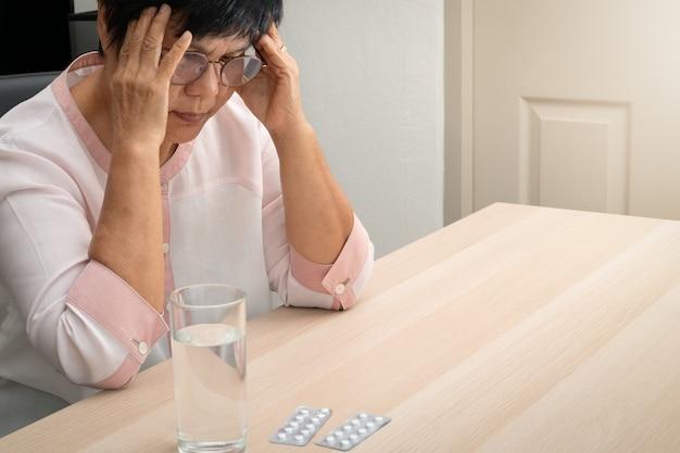 Velha mulher que sofre de dor de cabeça, estresse, enxaqueca, conceito de problema de saúde Foto Premium
