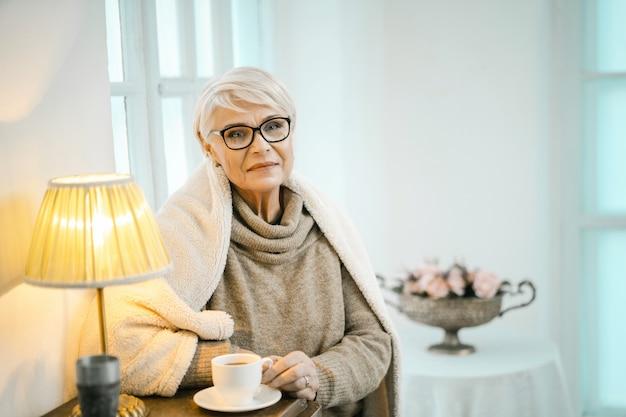 Velha mulher relaxando em casa e bebendo chá Foto Premium