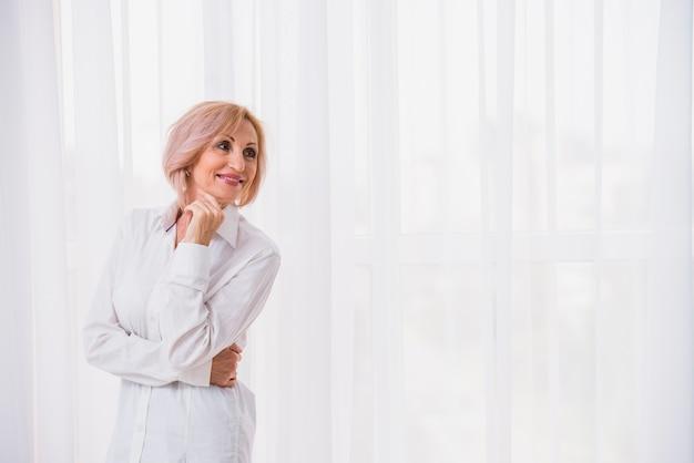 Velha senhora com cabelo curto, olhando feliz com espaço de cópia Foto gratuita