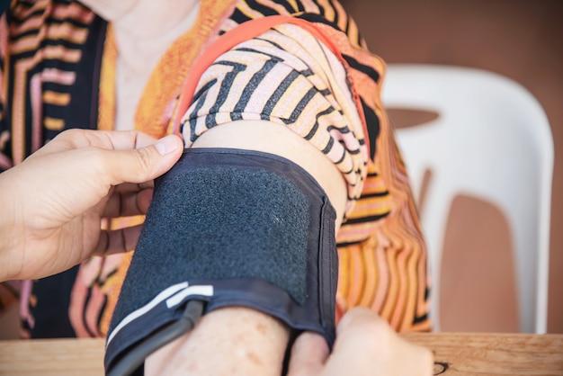 Velha senhora está sendo verificado a pressão arterial usando o conjunto de criança de monitor de pressão arterial Foto gratuita