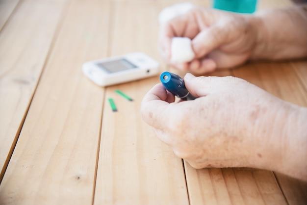 Velha senhora está testando o nível de açúcar no sangue usando o conjunto de criança de teste de açúcar no sangue Foto gratuita