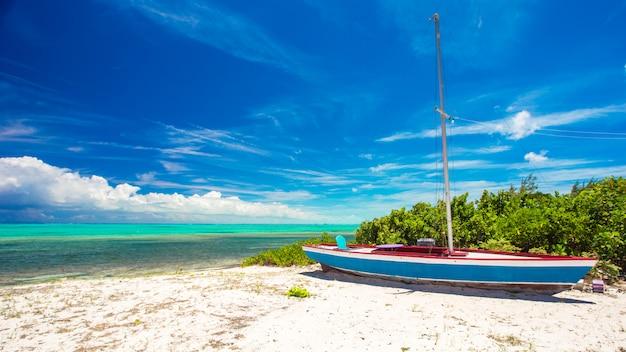 Velho barco de pesca em uma praia tropical no caribe Foto Premium