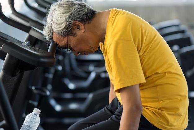 Velho cansado sofre de ataque cardíaco no ginásio Foto Premium
