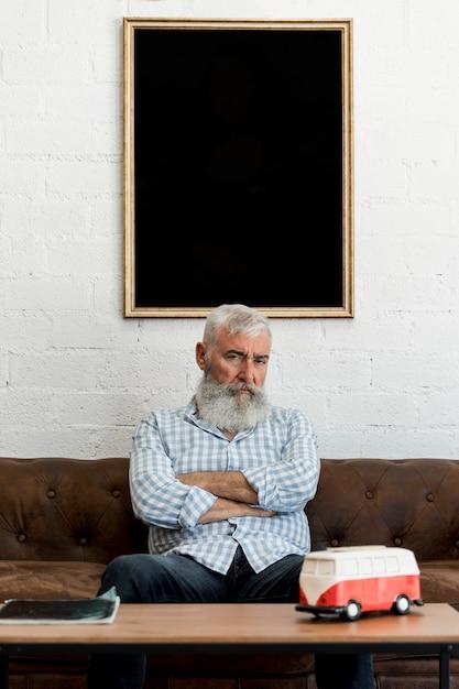 Velho cliente sentado no sofá no salão de cabeleireiro Foto gratuita