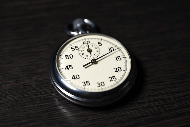 Velho cronômetro analógico encontra-se em uma superfície de madeira escura, close-up Foto Premium