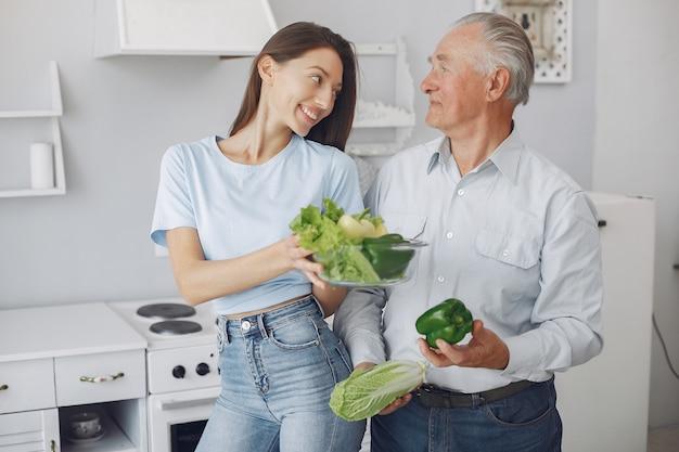 Velho em uma cozinha com jovem neta Foto gratuita