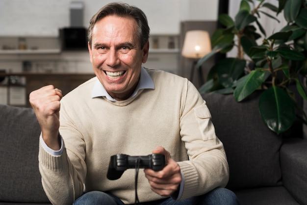 Velho feliz jogando videogame Foto gratuita