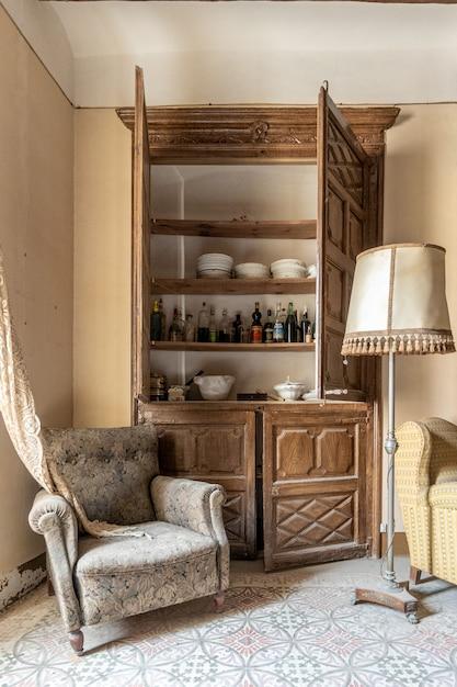 Velho guarda-roupa de uma casa clássica com bebidas e um sofá confortável e velho Foto Premium