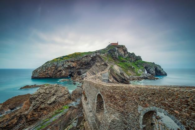 Velho muro de pedra atravessando o oceano para uma ilha Foto gratuita