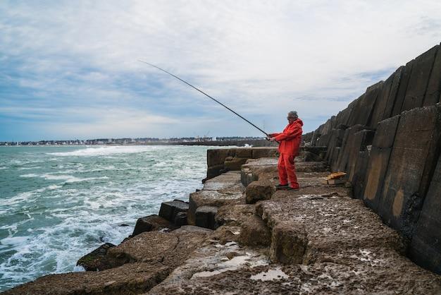 Velho pesca no mar. Foto Premium