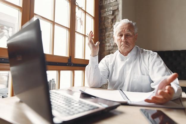 Velho sentado à mesa e trabalhando com um laptop Foto gratuita