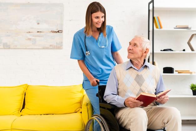 Velho sentado na cadeira de rodas enquanto fala para enfermeira Foto gratuita