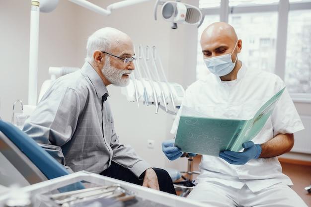 Velho sentado no consultório do dentista Foto gratuita