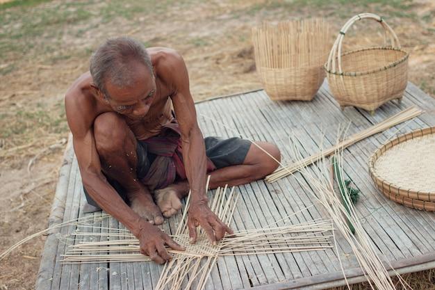 Velho tio asiático com ferramentas de vime. Foto Premium